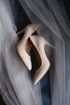 Beżowe buty panny młodej pięknie położone na zasłonie. dzień ślubu.