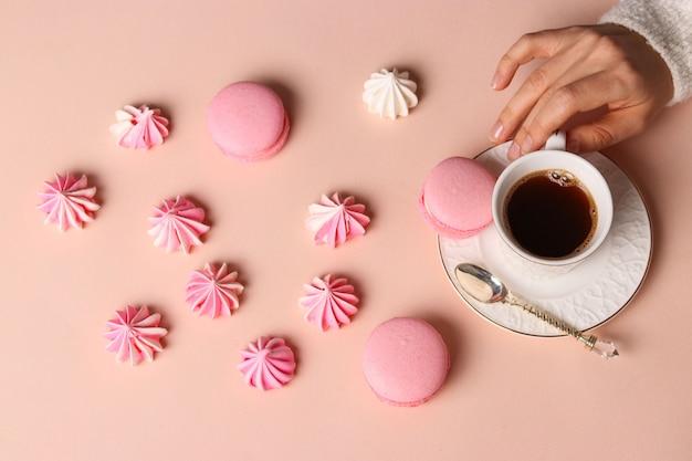 Bezowe ciasteczka i makaroniki, filiżanka kawy i dłonie kobiet