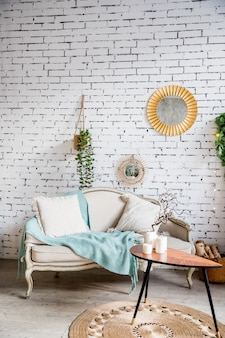 Beżowe i teksturowe poduszki na beżowej kanapie, miętowy koc. mały stół ze świecami. stylowe wnętrze salonu z sofą, poduszkami, eleganckimi akcesoriami osobistymi i roślinami na ścianie z cegły.