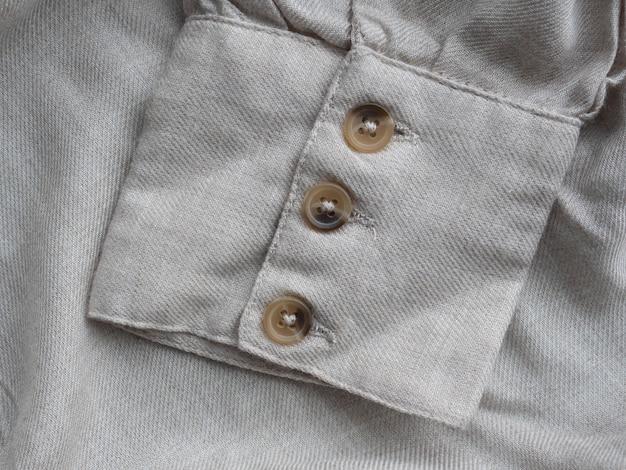 Beżowe mankiety z trzema guzikami na szarej koszuli z organicznego lnu
