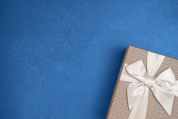 Beżowe pudełko ze wstążką na niebieskim tle.