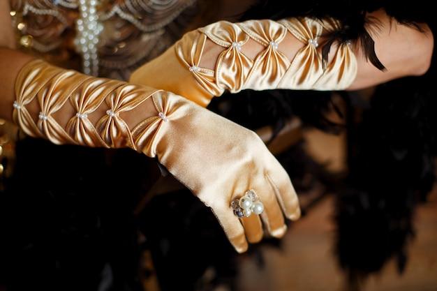 Beżowe satynowe rękawiczki na łokciach dłoni, ozdobione koralikami