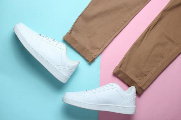 Beżowe spodnie, białe trampki na kolorowym pastelowym stole, modny wygląd, widok z góry, minimalizm