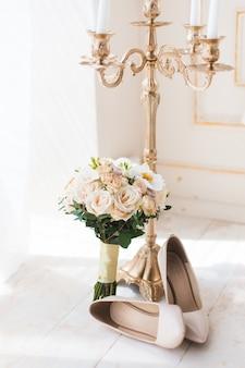 Beżowe szpilki czółenka z bukietem ślubnym i świecznikiem w porannym słońcu