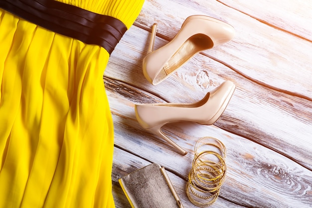 Beżowe szpilki i żółta sukienka. zestaw damskich bransoletek i obuwia. wyprzedaż sezonowa z dużymi rabatami. oferta specjalna w lokalnym butiku.