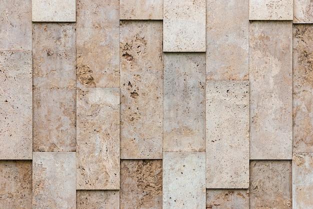 Beżowo-szara ściana z naturalnych kostek kamiennych o nieregularnym układzie