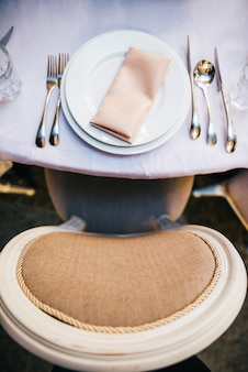 Beżowy krzesło stoi na stole z białą zastawą