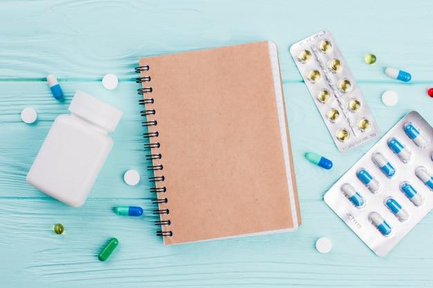 Beżowy notatnik otoczony jest różnymi pigułkami na niebieskim tle. tabletki w blistrze.
