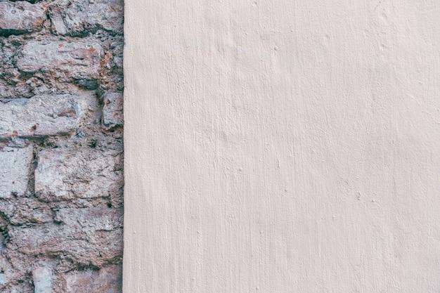 Beżowy nowy, otynkowany stary mur z cegły