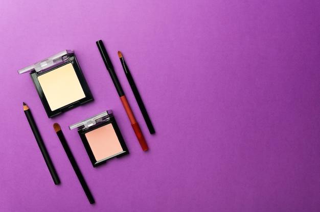 Beżowy puder do twarzy, róż, eyeliner i profesjonalny pędzel maquillage na fioletowo