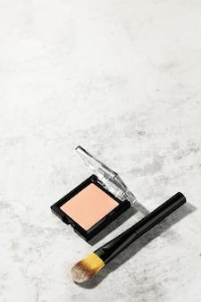 Beżowy puder do twarzy w kwadratowym etui z profesjonalnym pędzelkiem do makijażu