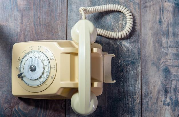 Beżowy stary telefon na drewnianym