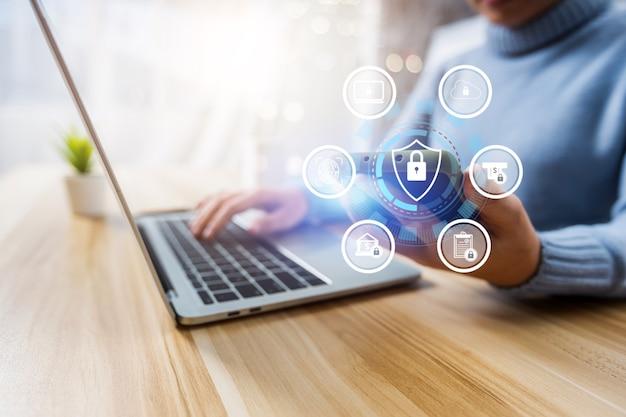 Bezpieczeństwo danych cybernetycznych i koncepcja technologii z ikoną, z bliska wygląd kobiety i naciśnięcie hasła w komputerze i przytrzymanie telefonu w celu uzyskania numeru seryjnego