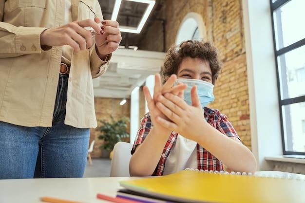 Bezpieczeństwo jest ważne, zabawny mały chłopiec w szkole, noszący maskę ochronną, myjący ręce kobieta