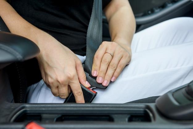 Bezpieczeństwo na drodze. kierowca kobieta, zapinanie pasów bezpieczeństwa, siedząc w samochodzie