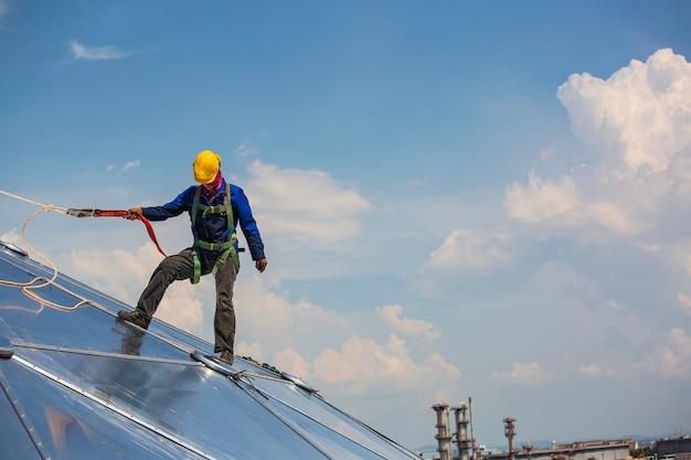 Bezpieczeństwo na wysokości z dostępem linowym dla pracowników płci męskiej, połączenie z uprzężą bezpieczeństwa z węzłem, wpięcie w system zabezpieczenia przed upadkiem z dachu i system punktów kotwiczenia zabezpieczających przed upadkiem gotowy do wznoszenia, kopuła zbiornika oleju na placu budowy
