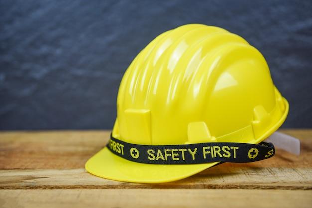 Bezpieczeństwo pierwszy żółty kask bezpieczeństwa nosić kask kapelusz pracownika inżynier na drewniane