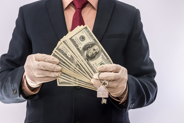 Bezpieczeństwo sprzedaży lub wynajęcia mężczyzna w rękawiczkach medycznych trzyma klucz do domu i dolara. ncov-2019