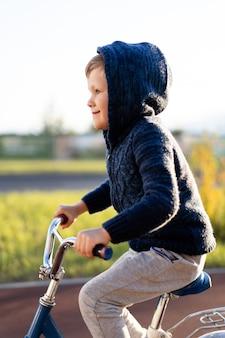Bezpieczeństwo w nowoczesnym europejskim mieście. mały szczęśliwy chłopiec jeździ rowerem po bezpiecznej gumowanej ścieżce rowerowej