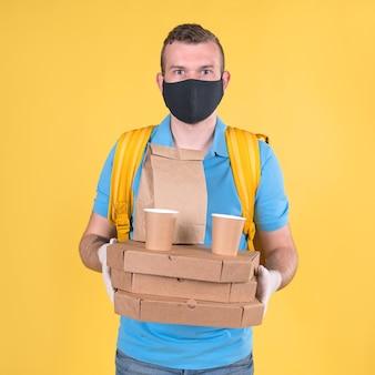 Bezpieczna dostawa jedzenia. nieogolony kaukaski młody blond facet dostarczający jedzenie w niebieskim mundurze