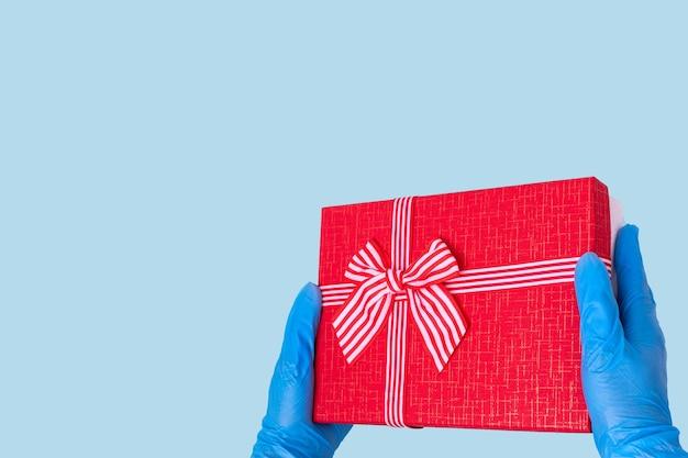 Bezpieczna dostawa koncepcji prezentów. ręce w niebieskich rękawiczkach trzymają czerwone pudełko z kokardą
