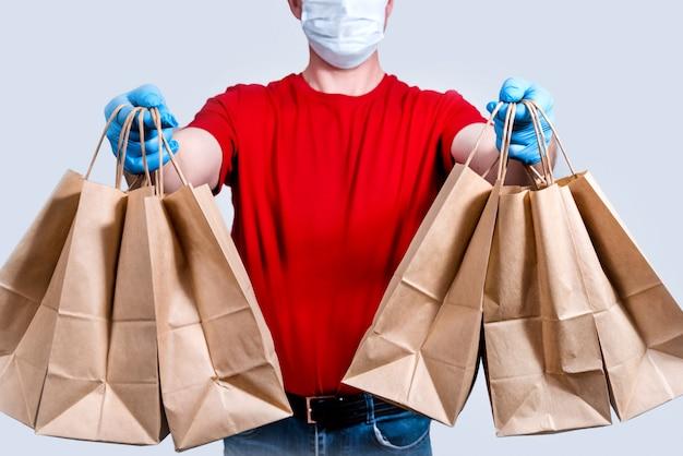 Bezpieczna dostawa kurier w czerwonym mundurze i ochronnej masce i rękawiczkach trzyma duże zamówienie, wiele papierowych torebek, bezdotykowe dostawy żywności w kwarantannie.