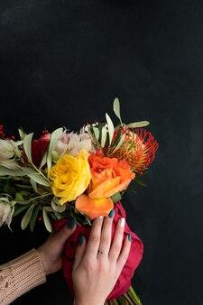 Bezpieczna i szybka dostawa bukietu kwiatów dla bliskiej ci osoby. kobiece ręce trzymające kreatywną kompozycję róż dalii i liści na czarnym tle