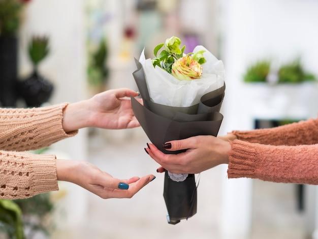 Bezpieczna i szybka dostawa bukietu kwiatów dla bliskiej ci osoby. kobiece ręce trzymające kreatywny układ róż dalii i jagód
