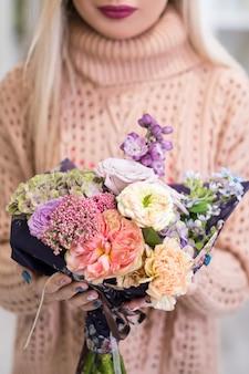Bezpieczna i szybka dostawa bukietu kwiatów dla bliskiej ci osoby. kobiece ręce trzymające twórczą aranżację róż, piwonii, hortensji i bzu