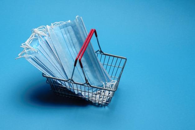 Bezpieczne i internetowe zakupy na koncepcji kwarantanny. kosz na zakupy z ochronną maską medyczną na niebieskim tle