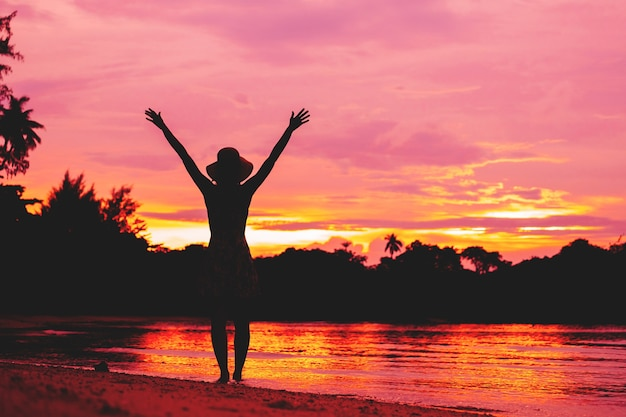 Bezpłatna szczęśliwa kobieta podnosząca ręce oglądając zachód słońca