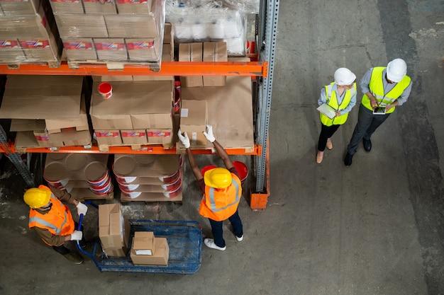Bezpośrednio nad widokiem pracowników magazynu w kamizelkach odblaskowych i kaskach pracujących ze sobą podczas dystrybucji towarów