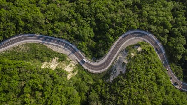 Bezpośrednio nad widokiem samochodów jadących po zygzakowatej krętej górskiej drodze