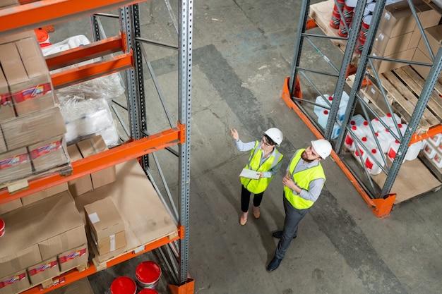 Bezpośrednio nad widokiem współpracowników w zielonych kamizelkach i kaskach, dyskutujących o nowych dostawach w magazynie, patrząc na pudełka na półkach