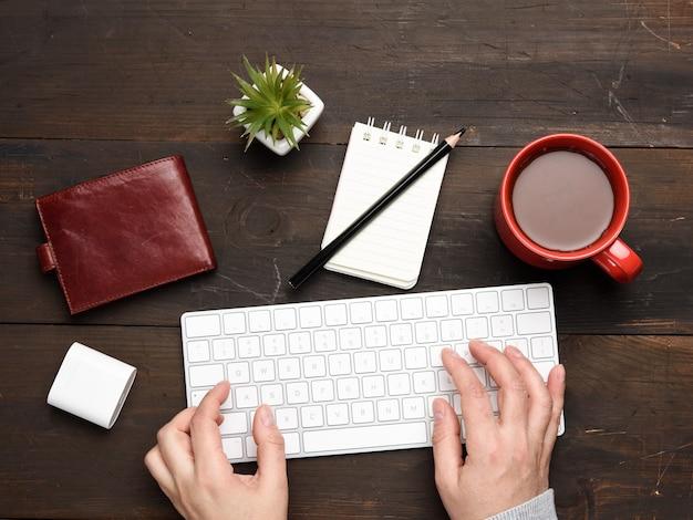 Bezprzewodowa klawiatura i dwie ręce piszą na drewnianym stole