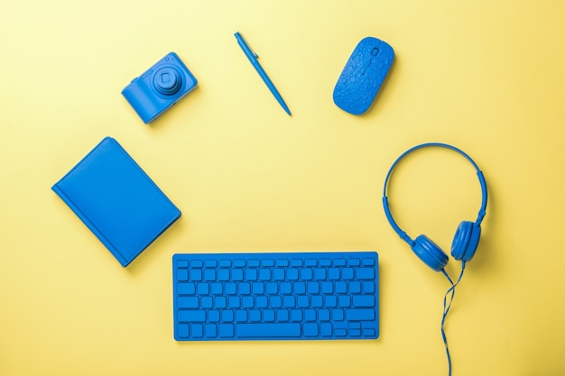 Bezprzewodowa klawiatura i mysz, słuchawki i kamera na żółtej powierzchni. stylowe akcesoria dla biznesu i freelancerów. leżał na płasko.