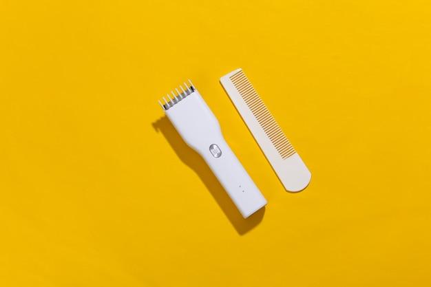 Bezprzewodowa maszynka do strzyżenia włosów i grzebień na żółty jasny.