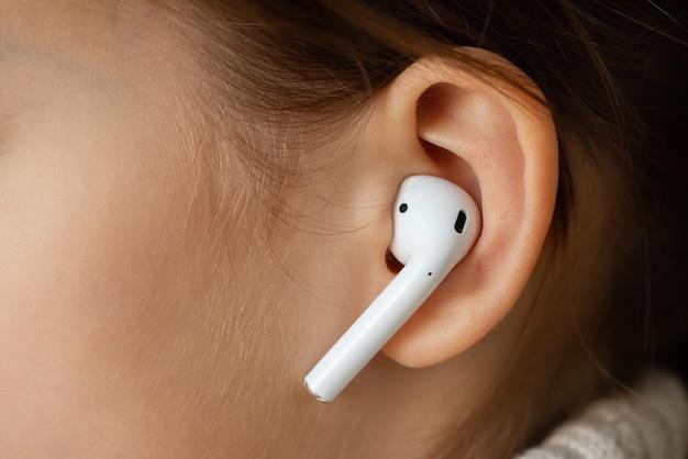 Bezprzewodowa słuchawka w uchu dziewczynki