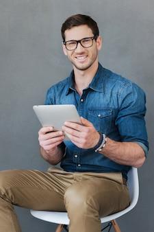 Bezprzewodowa wolność. szczęśliwy młody człowiek trzymający cyfrowy tablet i patrzący na kamerę