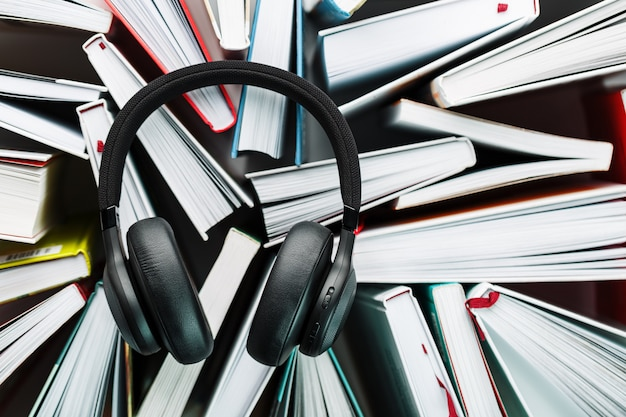 Bezprzewodowe, czarne słuchawki leżą na książkach. koncepcja uczenia się za pomocą audiobooka. aby posłuchać książki.