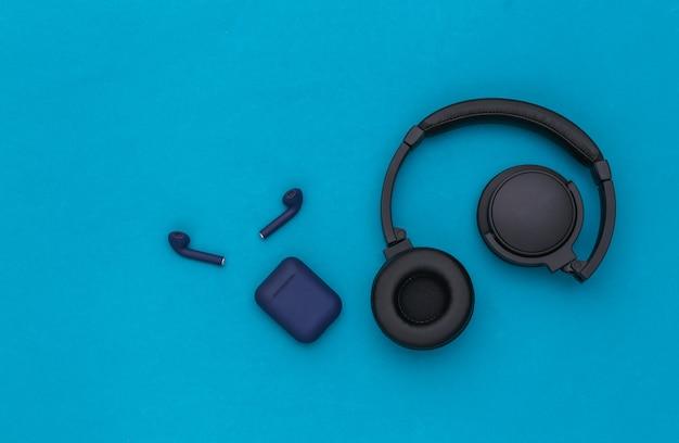 Bezprzewodowe duże słuchawki stereo i małe słuchawki douszne z etui na ładowarkę na niebieskim tle. widok z góry