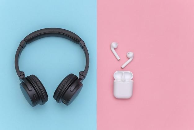 Bezprzewodowe duże słuchawki stereo i małe słuchawki douszne z etui na ładowarkę na różowym niebieskim pastelowym tle. widok z góry