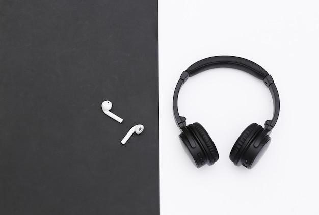 Bezprzewodowe duże słuchawki stereo i małe wkładki douszne na czarno białym tle. widok z góry