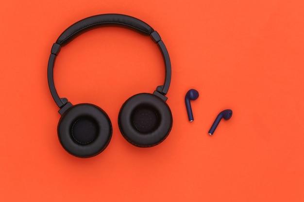 Bezprzewodowe duże słuchawki stereo i małe wkładki douszne na pomarańczowym tle. widok z góry