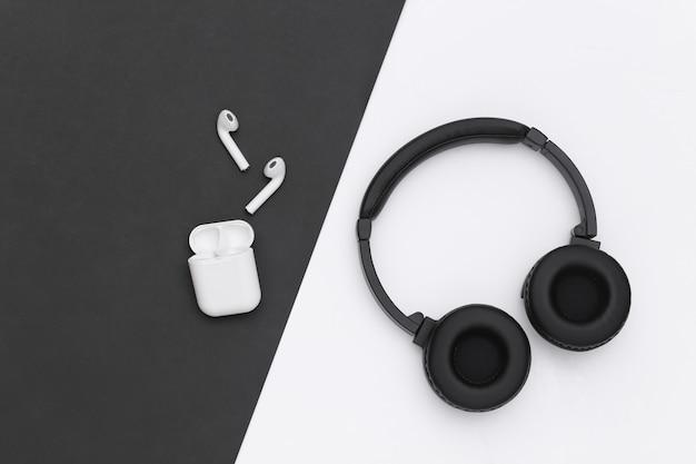 Bezprzewodowe duże słuchawki stereo i małe wkładki douszne z etui na ładowarkę na czarno białym tle. widok z góry