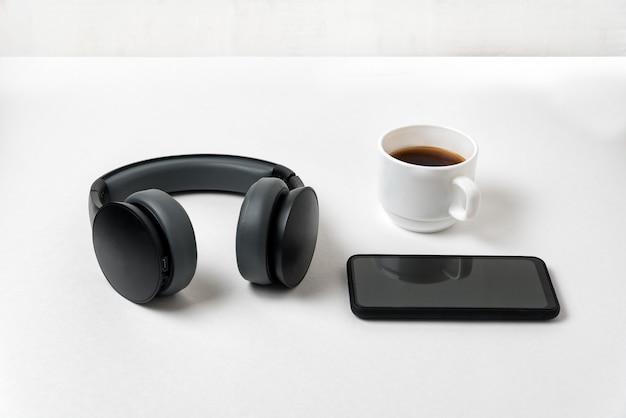 Bezprzewodowe pełnowymiarowe słuchawki, telefon i filiżanka kawy
