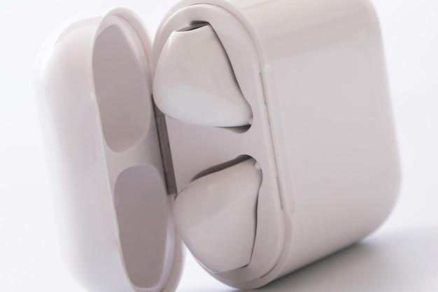 Bezprzewodowe słuchawki douszne z etui ładującym na białej powierzchni
