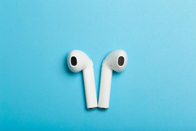Bezprzewodowe słuchawki dźwiękowe na kolorowym słuchaniu aplikacji muzycznej w tle