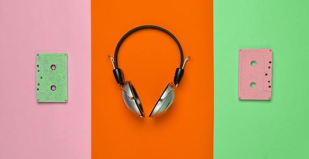 Bezprzewodowe słuchawki i kasety audio na wielokolorowym pastelowym papierze.