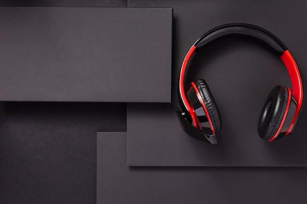 Bezprzewodowe słuchawki lub słuchawki na abstrakcyjnym czarnym tle papieru, styl koncepcji minimalizmu